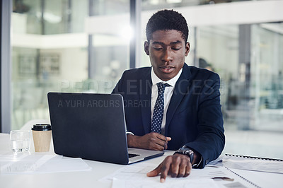 Buy stock photo Shot of a young businessman going through paperwork in an office