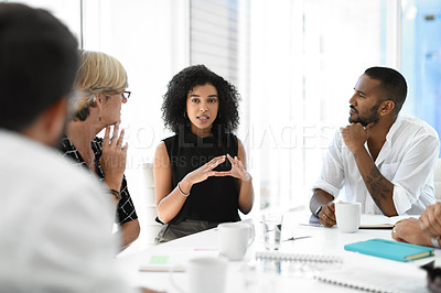 Buy stock photo Cropped shot of an attractive young businesswoman brainstorming with her colleagues during a meeting in the boardroom