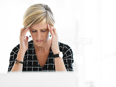 Buy stock photo Cropped shot of an attractive mature businesswoman suffering with a headache while working in her office