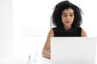 Buy stock photo Cropped shot of an attractive young businesswoman looking serious while working on a laptop in her office