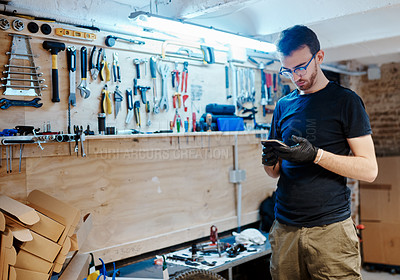 Buy stock photo Shot of a young man using a cellphone in a bicycle workshop