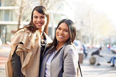 Buy stock photo Cropped portrait of two affectionate young friends smiling while standing together outdoors in the city