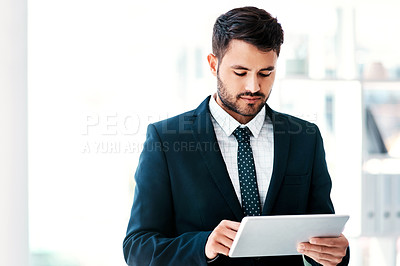 Buy stock photo Cropped shot of a handsome young businessman using a digital tablet while standing in a modern office