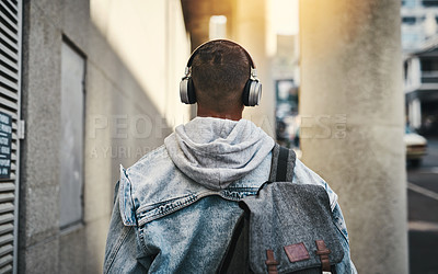 Buy stock photo Rearview shot of a man wearing his headphones while out in the city