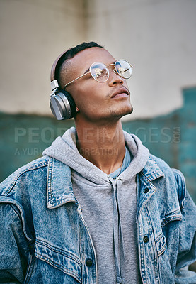 Buy stock photo Shot of a young man wearing his headphones while out in the city
