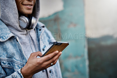 Buy stock photo Cropped shot of a handsome young man using his cellphone while out in the city