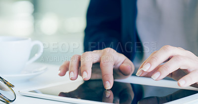 Buy stock photo Cropped shot of an unrecognizable businesswoman sitting alone and typing on her tablet in the office