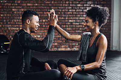 Buy stock photo Shot of a young man and woman giving each other a high five at the gym