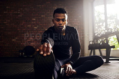 Buy stock photo Shot of a young man doing his warmup exercises at the gym