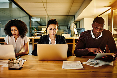 Buy stock photo Cropped shot of a diverse group of businesspeople sitting together and using technology during a late night in the office