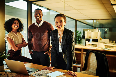 Buy stock photo Cropped shot of a diverse group of business colleagues standing together during a late night in the office