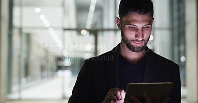 Buy stock photo Cropped shot of a handsome young businessman standing alone and using a tablet after a late shift in the office
