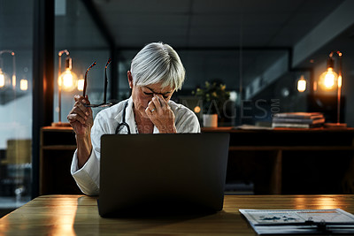 Buy stock photo Shot of a mature female doctor feeling stressed out while working on a laptop inside her office at night