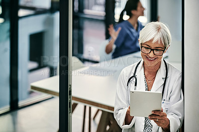 Buy stock photo Shot of a mature female doctor using a digital tablet inside a hospital with her colleagues in the background