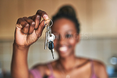 Buy stock photo Cropped shot of a young woman holding up the keys to her new home