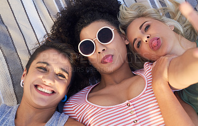 Buy stock photo Cropped shot of three friends lying together on a picnic blanket