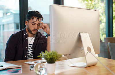 Buy stock photo Cropped shot of a handsome young businessman feeling overwhelmed and falling asleep while sitting at his computer in his office