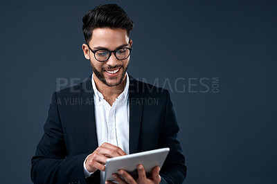 Buy stock photo Cropped shot of a handsome young businessman standing alone and using a tablet against a gray background in the studio