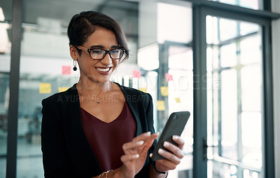 Buy stock photo Cropped portrait of an attractive young businesswoman standing alone in her office and texting on her cellphone