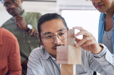 Buy stock photo Shot of a group of young businesspeople having a meeting with building blocks in a modern office