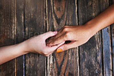 Buy stock photo High angle shot of two unrecognizable women holding hands in comfort on a table outdoors