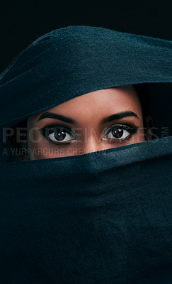 Buy stock photo Cropped shot of an attractive young woman wearing a hijab and only exposing her eyes while against a black background