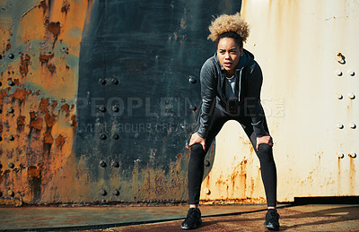 Buy stock photo Shot of a young woman standing with her hands on her knees after a run