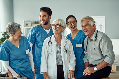 Buy stock photo Cropped shot of a group of cheerful doctors standing together while laughing inside of a doctor's office during the day