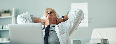 Buy stock photo Cropped shot of a carefree mature male doctor seated at a desk with his hands behind his head inside of a doctor's office