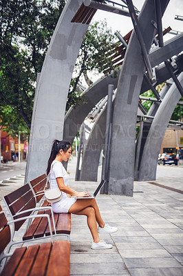 Buy stock photo Full length shot of an attractive young woman wearing earphone and sitting on a street bench while using her laptop