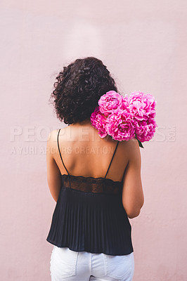 Buy stock photo Rearview shot of a young woman holding a bouquet of flowers against a pink background