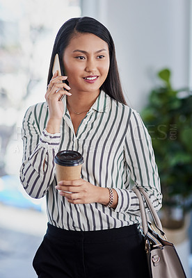 Buy stock photo Shot of an attractive young businesswoman drinking coffee and making a phone call in her office
