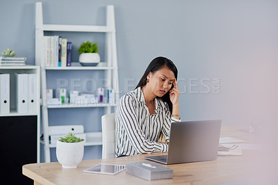 Buy stock photo Shot of an attractive young businesswoman feeling stressed out and suffering from a headache while working inside her office