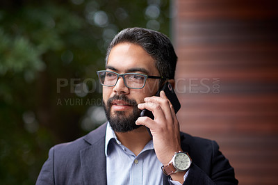 Buy stock photo Shot of a mature businessman talking on a cellphone outdoors