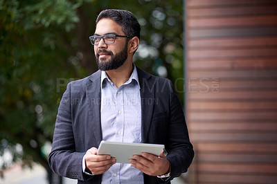 Buy stock photo Shot of a mature businessman using a digital tablet outdoors
