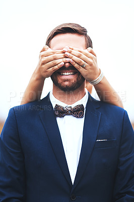 Buy stock photo Shot of a happy bridegroom getting his eyes covered by his bride on their wedding day