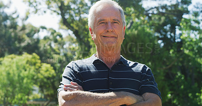 Buy stock photo Cropped portrait of a cheerful senior man standing with his arms crossed in a park during the day