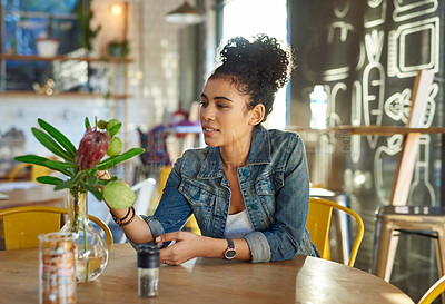 Buy stock photo Cropped shot of an attractive young woman sitting alone in a coffee shop and admiring the flowers