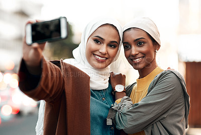 Buy stock photo Cropped shot of two attractive young women standing together and wearing headscarves while taking a selfie with their cellphone