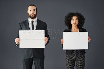 Buy stock photo Studio portrait of two young corporate businesspeople holding blank placards against a grey background
