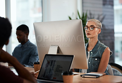 Buy stock photo Shot of an attractive young businesswoman working on a computer inside a modern office with colleagues in the background