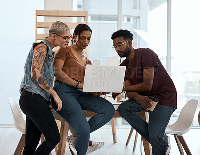 Buy stock photo Shot of a group of creative young businesspeople working on a laptop together inside a modern office