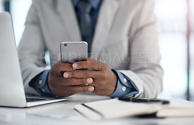 Buy stock photo Cropped shot of a businessman using a smartphone and laptop in a modern office