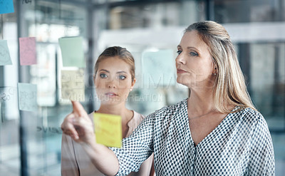 Buy stock photo Shot of two businesswomen having a brainstorming session in a modern office