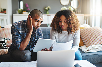 Buy stock photo Cropped shot of a stressed young couple sitting together and using a laptop to go over their financial paperwork