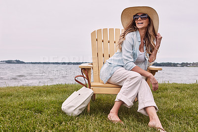 Buy stock photo Shot of a beautiful young woman relaxing on a chair next a lake