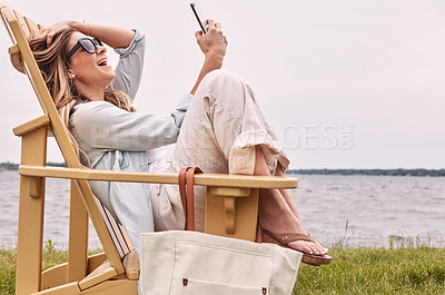 Buy stock photo Shot of an attractive young woman using a smartphone while relaxing next to the lake