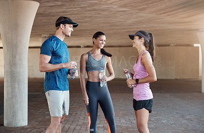 Buy stock photo Shot of a group of three people standing together while out for a workout together