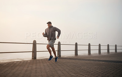 Buy stock photo Shot of a man out for a run on the promenade