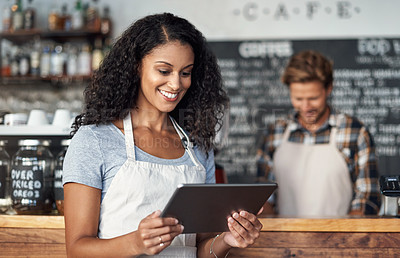 Buy stock photo Defocused shot of a young shop owner using a digital tablet while standing in her cafe